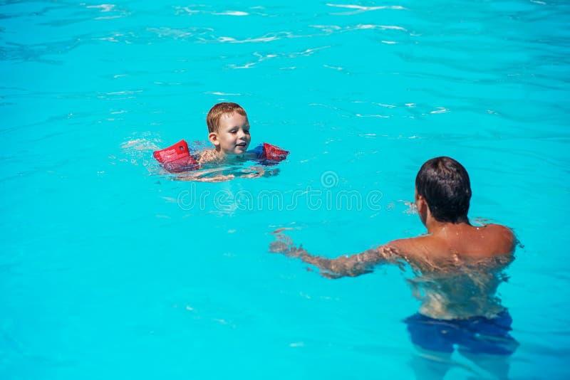 Farsa och son som har gyckel i swimmming pöl royaltyfria bilder