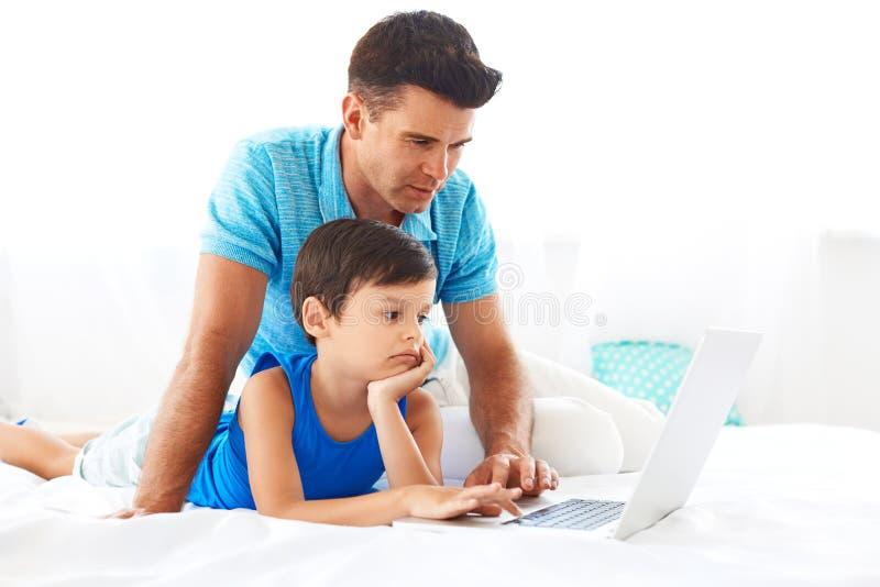 Farsa och son som har rolig användande PC arkivfoto