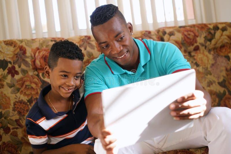Farsa och son som hemma spelar leken med bärbar datorPC royaltyfri fotografi