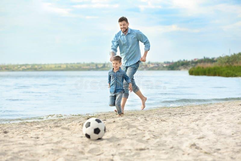 Farsa och son som spelar fotboll tillsammans fotografering för bildbyråer