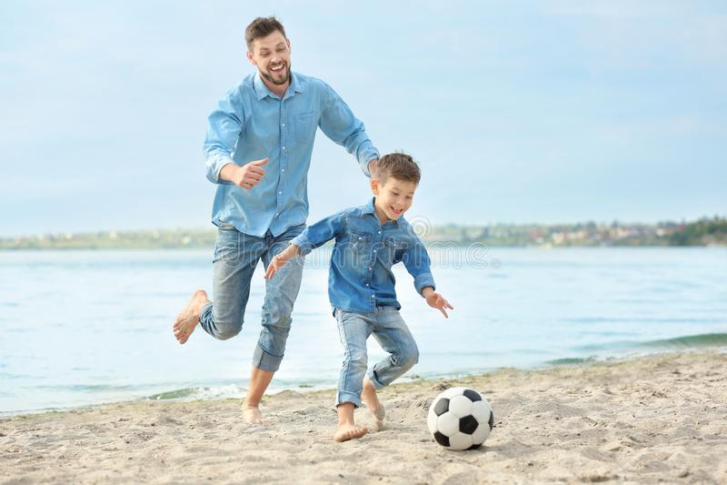 Farsa och son som spelar fotboll tillsammans arkivfoton