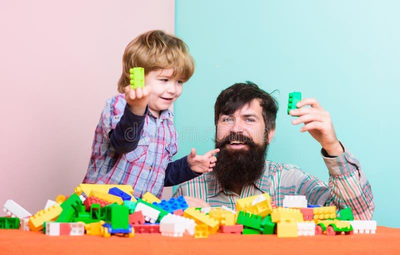 Farsa- och ungebyggande av plast- kvarter Fadern och sonen skapar f?rgrika konstruktioner med tegelstenar Barnav?rdutveckling arkivbild