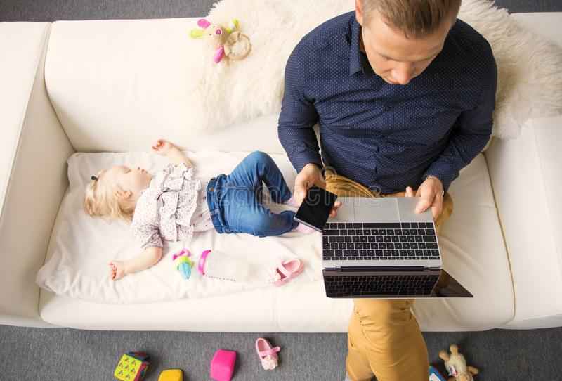 Farsa som arbetar på bärbara datorn, medan hans behandla som ett barn flickan som sover på soffan arkivfoton