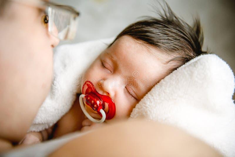 Farsa som rymmer den nyfödda sova dottern i hans armar royaltyfri foto