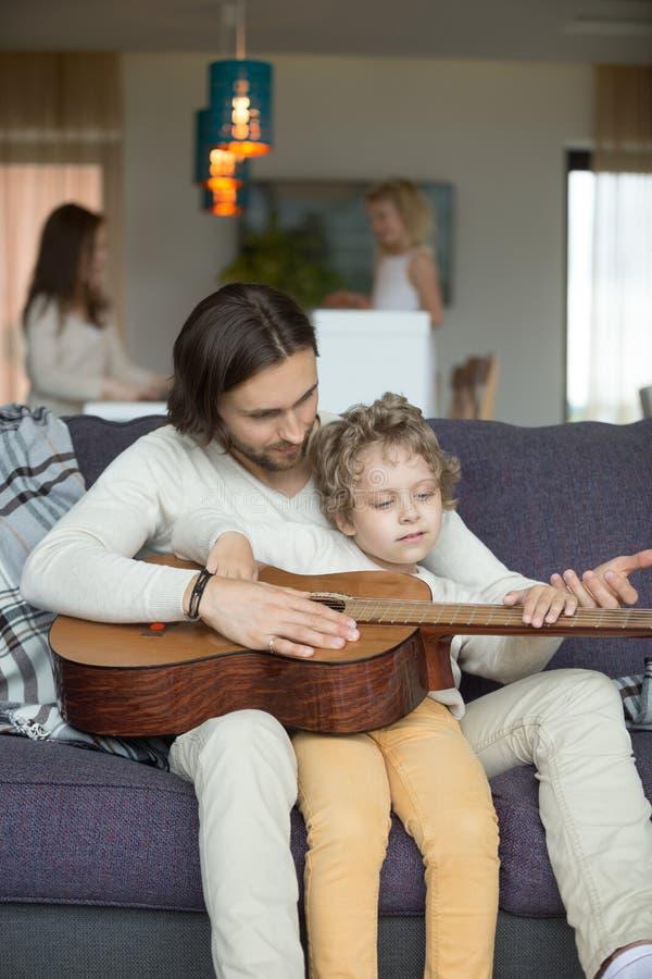 Farsa som undervisar den lilla sonlekgitarren, dottermatlagning som hjälper mo arkivfoton