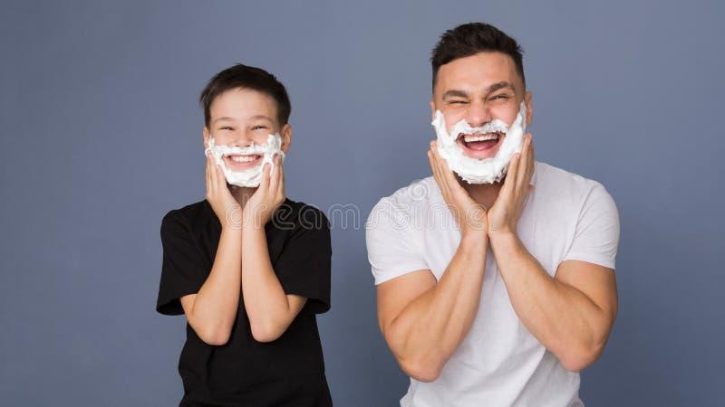 Farsa som undervisar hans son att raka och att sätta skum på framsidor royaltyfria foton