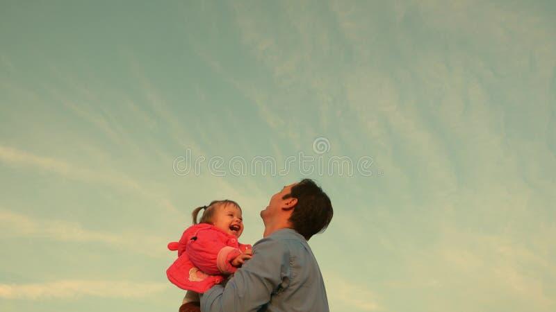 Farsadugg upp ett barn skyward fadern kastade behandla som ett barn till himlen lycklig begreppsfamilj Farsalekar med ungen royaltyfria bilder