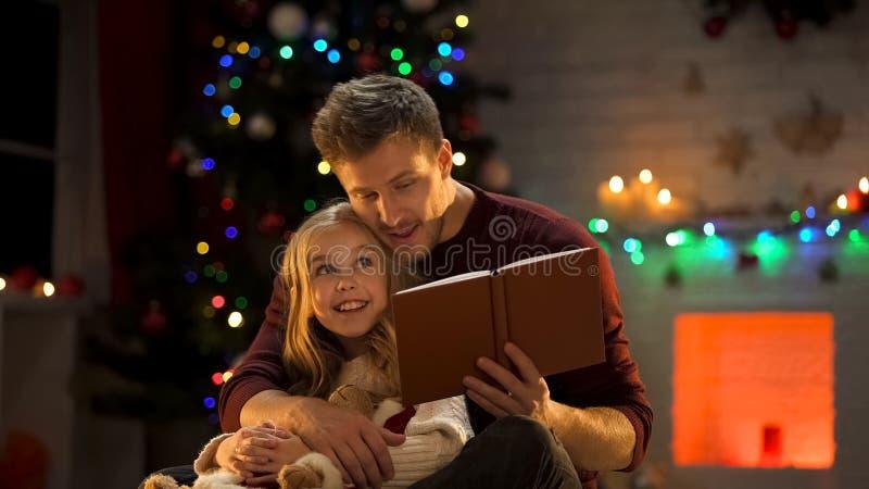 Farsaläsebok för förtjusande dotter nära julgranen, magisk atmosfär arkivfoton