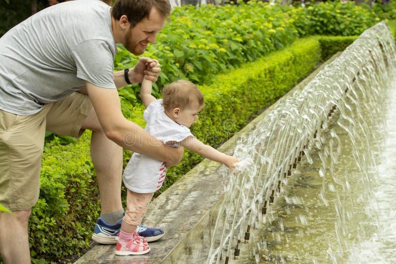 Farsan går med hans lilla dotter i parkerar med springbrunnar Behandla som ett barn flickan som 10 månader drar händer till strål royaltyfria foton