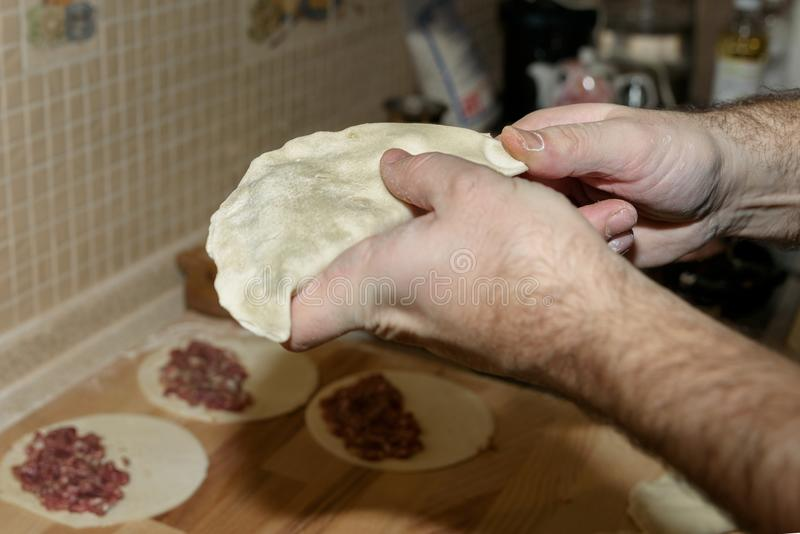 Farsan lagar mat chebureki Kock hemma Singelrundastycket av deg vek över fyllningen i en växande form Nationell maträtt av cet royaltyfri bild