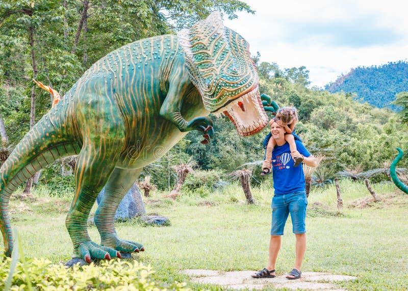 Farsan med den lilla dottern nära stor grön dinosaurie i parkerar på en solig dag r royaltyfria bilder