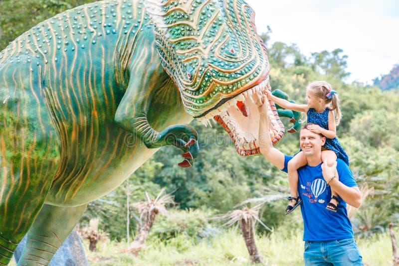 Farsan med den lilla dottern n?ra stor gr?n dinosaurie i parkerar p? en solig dag r fotografering för bildbyråer