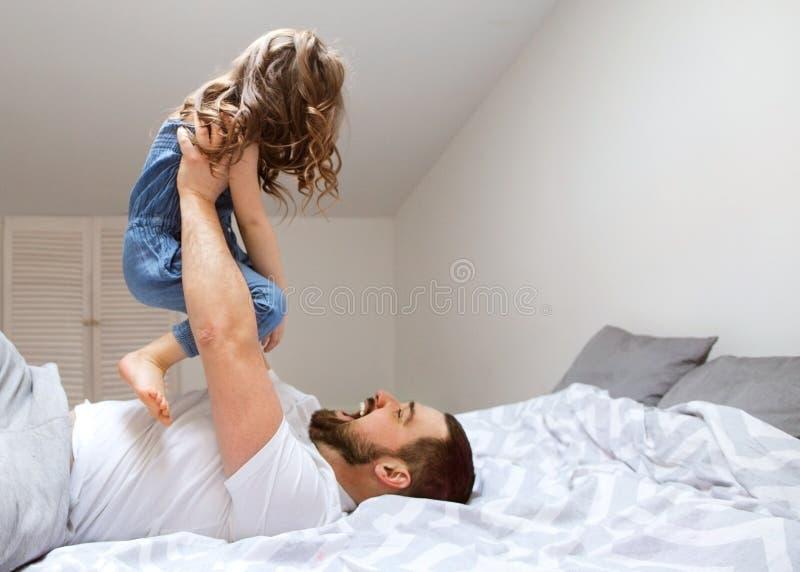 Farsan och dottern har roligt hemma på sängen dagfader s royaltyfri fotografi