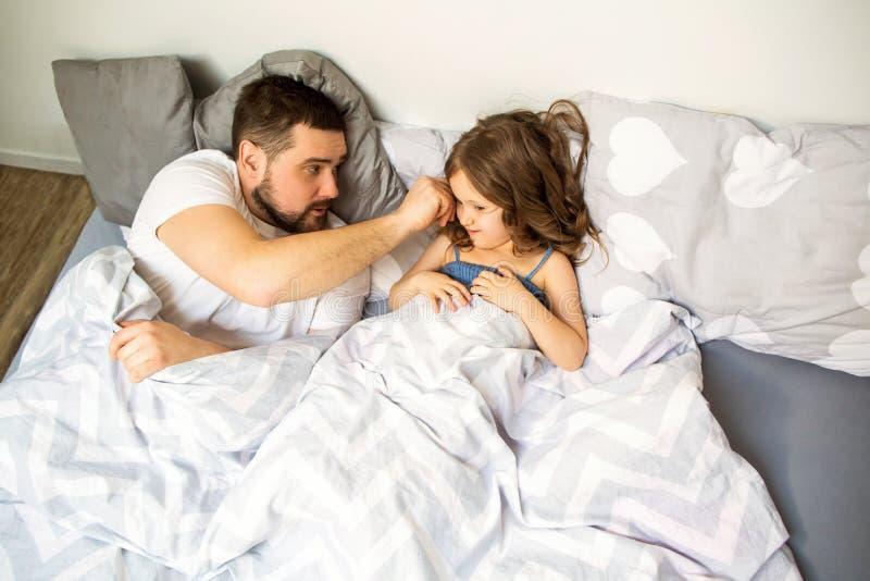 Farsan och dottern har roligt hemma på sängen dagfader s royaltyfri bild