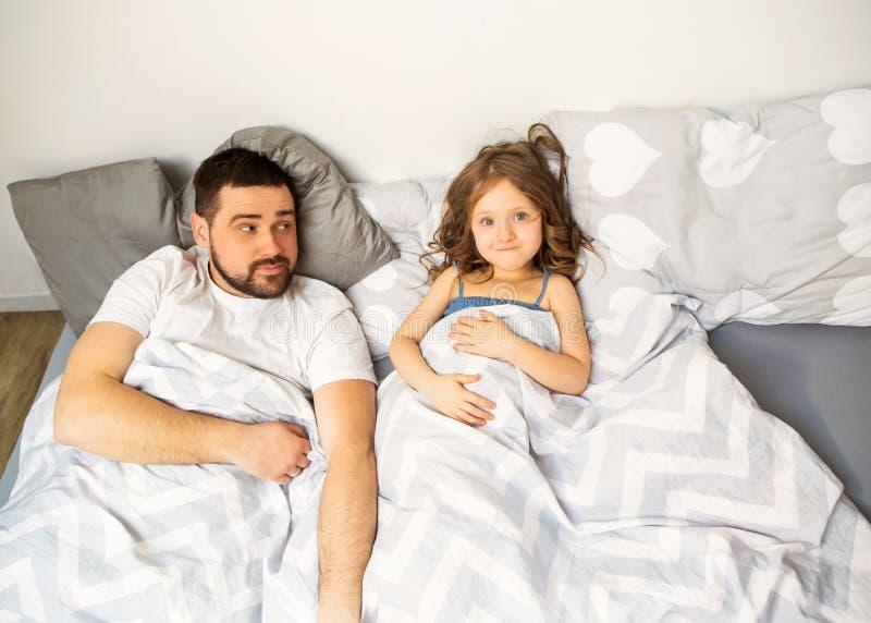 Farsan och dottern har roligt hemma på sängen dagfader s royaltyfria foton