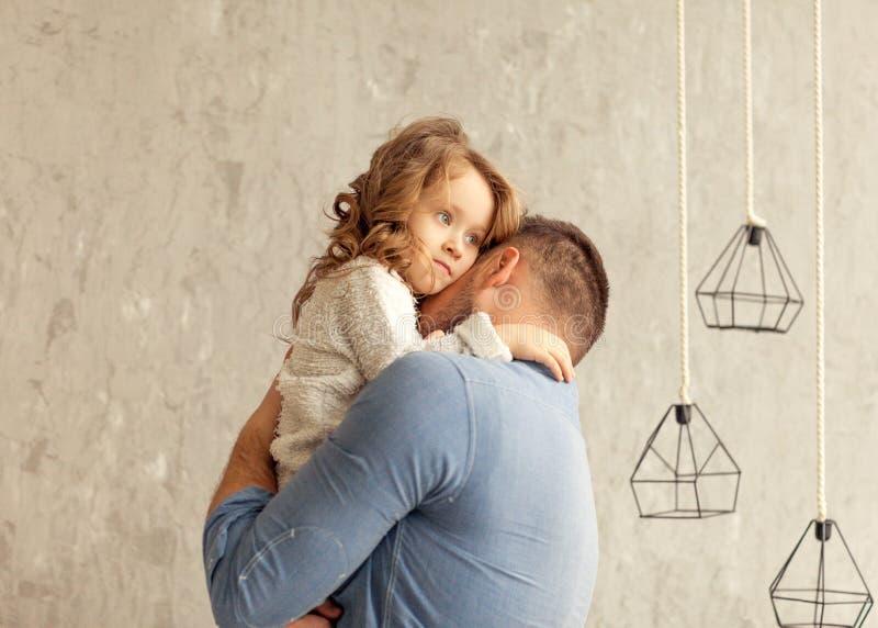 Farsan och dottern kramar hemma royaltyfri bild