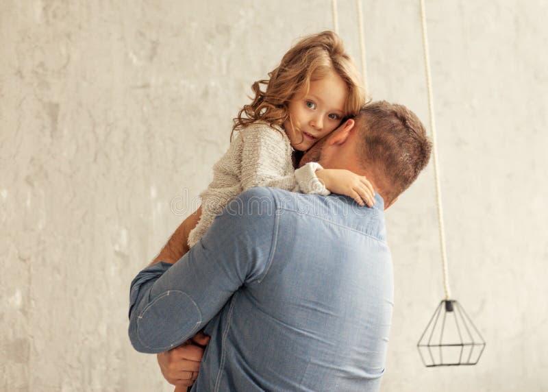 Farsan och dottern kramar hemma royaltyfri fotografi