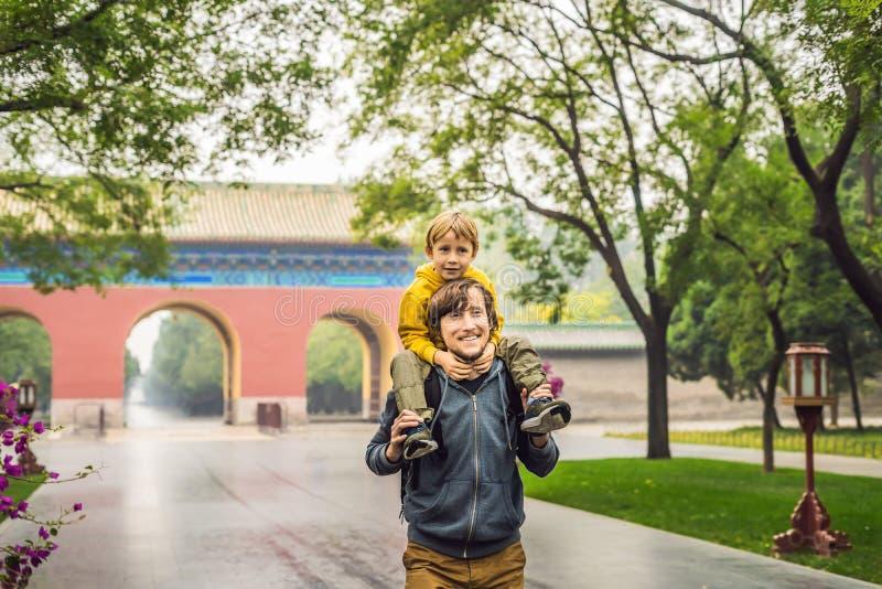 Farsan och sonen är turister på bakgrunden av de stora kinesiska portarna Lopp med barn i det Kina begreppet arkivbild