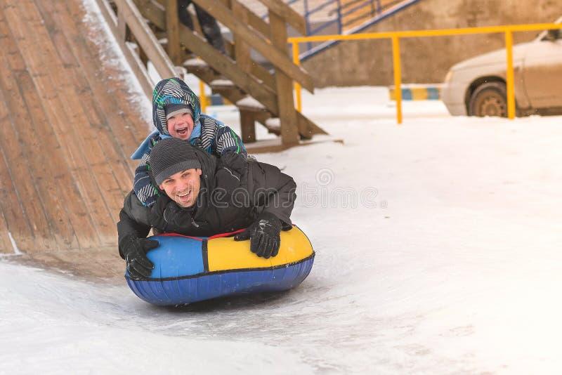 Farsan och sonen rullar i den snöig glidbanan på rör royaltyfri foto