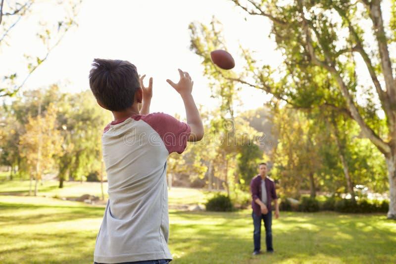 Farsan och sonen som kastar amerikansk fotboll i, parkerar till varandra arkivfoton
