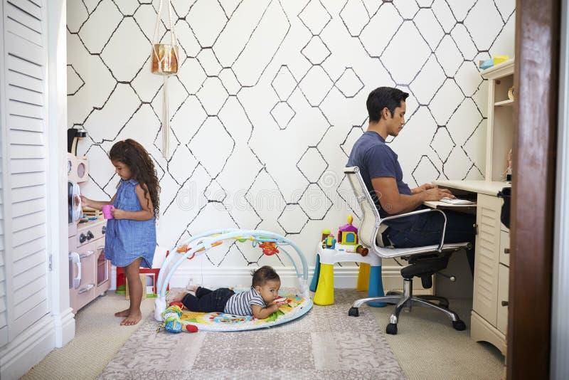 Farsan sitter att arbeta på ett skrivbord hemma, medan hans behandla som ett barn sonen och ung dotterlek i rummet bak honom fotografering för bildbyråer