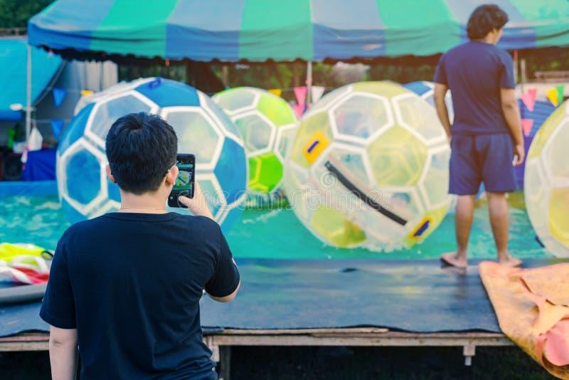 Farsan tar ett foto vid smartphonen av hans son som har gyckel i jätte- bubblaboll på vatten i pöl arkivfoton