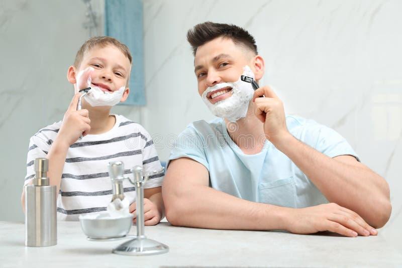 Farsaraka och son som in imiterar honom royaltyfria foton
