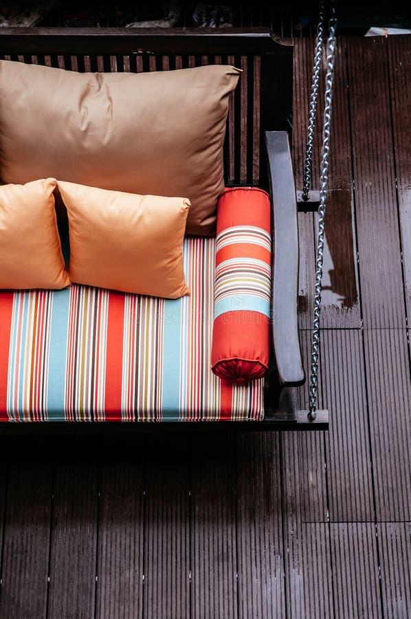 Farstubrogunga med färgglade kuddar och kuddar på träbalcon royaltyfria foton