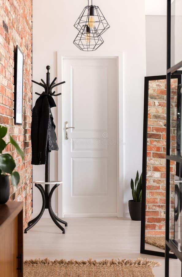 Farstuinre med lampor, spegeln, hängaren och den vita dörren royaltyfri fotografi