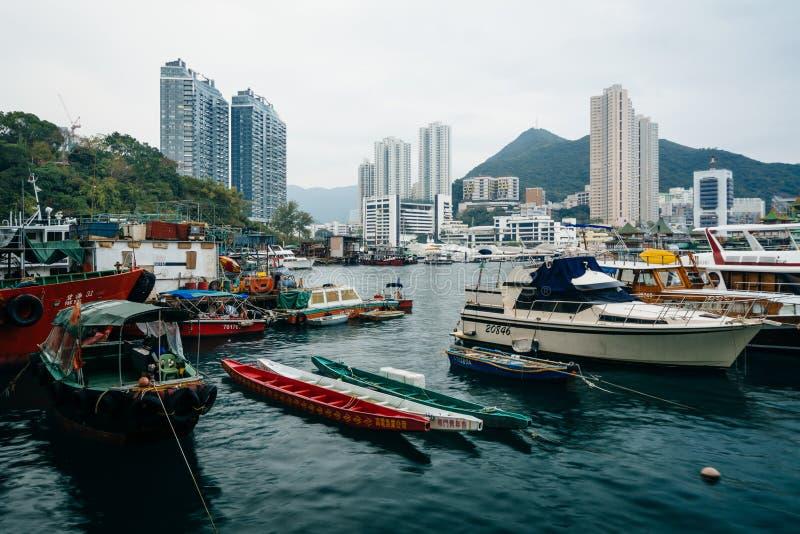 Fartyg anslöt på Ap Lei Chau och sikt av skyskrapor och berget arkivbilder