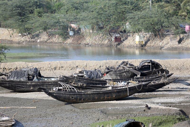 Fartyg av fiskare strandade i gyttjan på lågvatten på flodMalta den near staden på burk, Indien royaltyfri foto