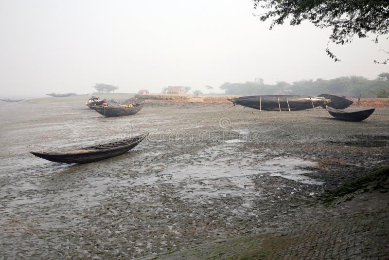 Fartyg av fiskare strandade i gyttjan på lågvatten på flodMalta den near staden på burk, Indien arkivbilder