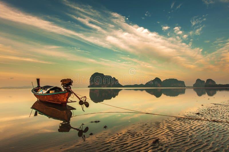 Fartyg för lång svans över färgrik himmel på stranden arkivfoton