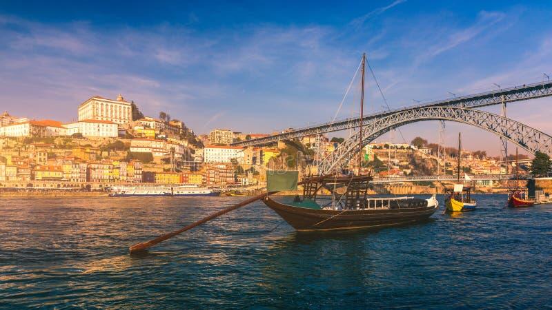 Fartyg för portvin på stranden med den Dom Luis bron och den gamla staden på den Douro floden i Ribeira i stadsmitten av Porto arkivfoton