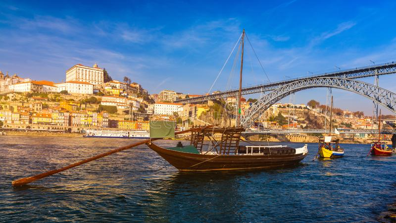Fartyg f?r portvin p? stranden med den Dom Luis bron och den gamla staden p? den Douro floden i Ribeira i stadsmitten av Porto royaltyfria foton