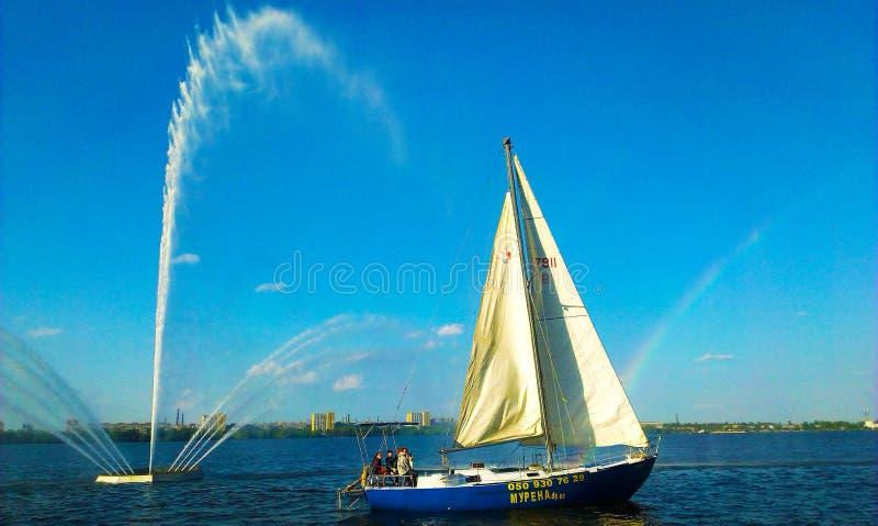 Fartyg i bakgrunden av en springbrunn med en regnbåge fotografering för bildbyråer