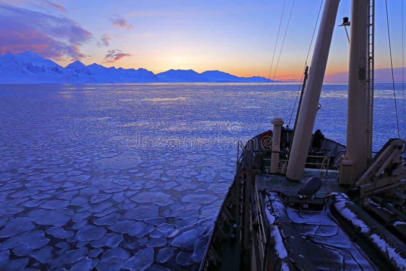 Fartyg i vinterarktisk Vitt snöig berg, blå glaciär Svalbard, Norge Is i havet Isbergskymning i nordpolen Rosa clo royaltyfria bilder
