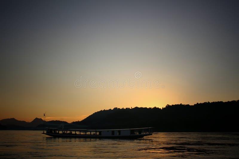 Fartyg längs Mekonget River i solnedgång arkivbilder