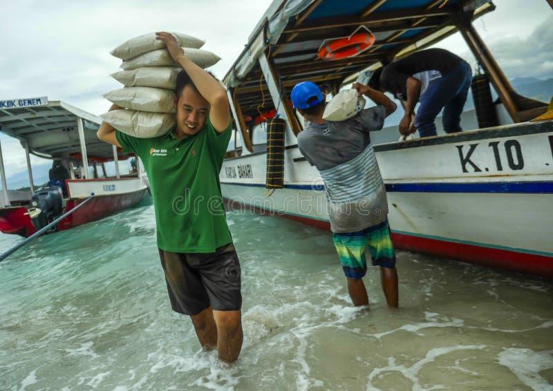 Fartyg levererar 24/7 all sort av material att kompensera bristen av resurser av ön Här besättningen som lastar av ris arkivfoton