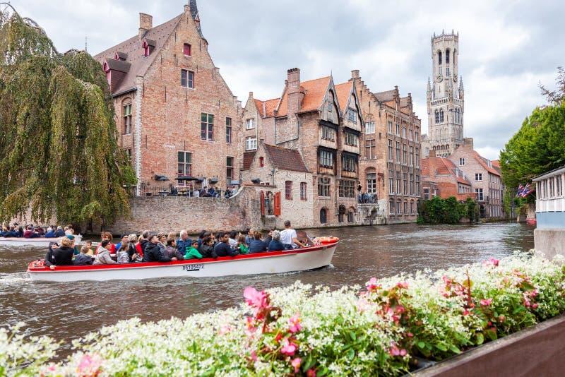 Fartyg mycket av turister i vattenkanalen av Bruges i Belgien arkivfoto