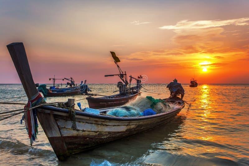Fartyg nära stranden på solnedgången arkivbilder