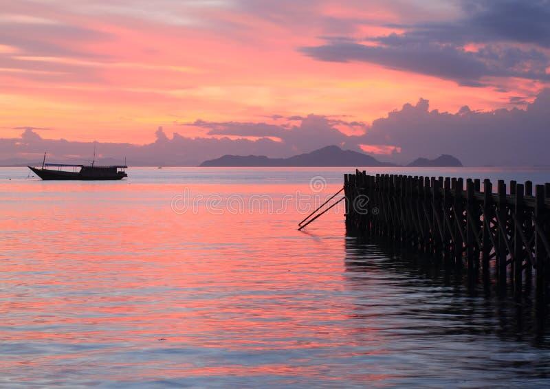 Fartyg och brygga på solnedgånghavet arkivbild