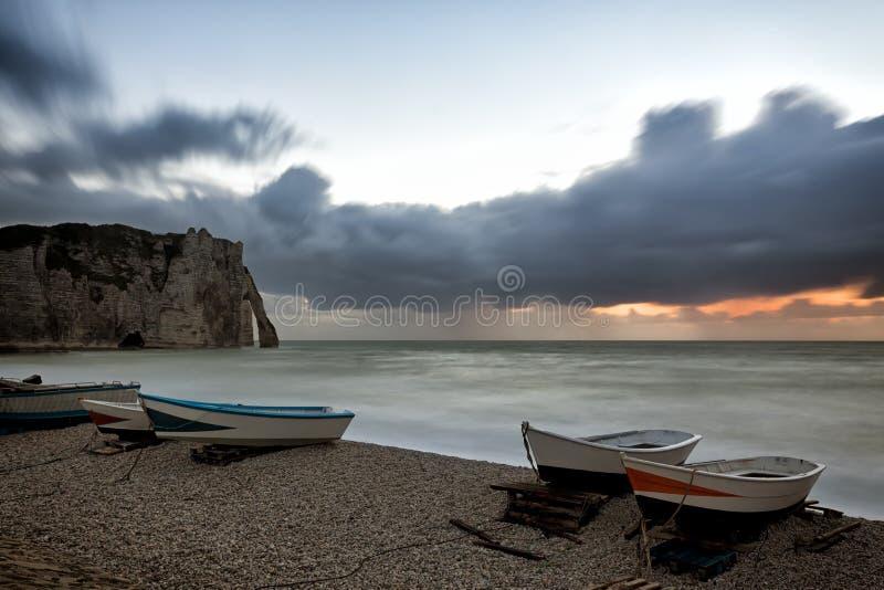Fartyg på den Etretat stranden på solnedgången arkivfoton