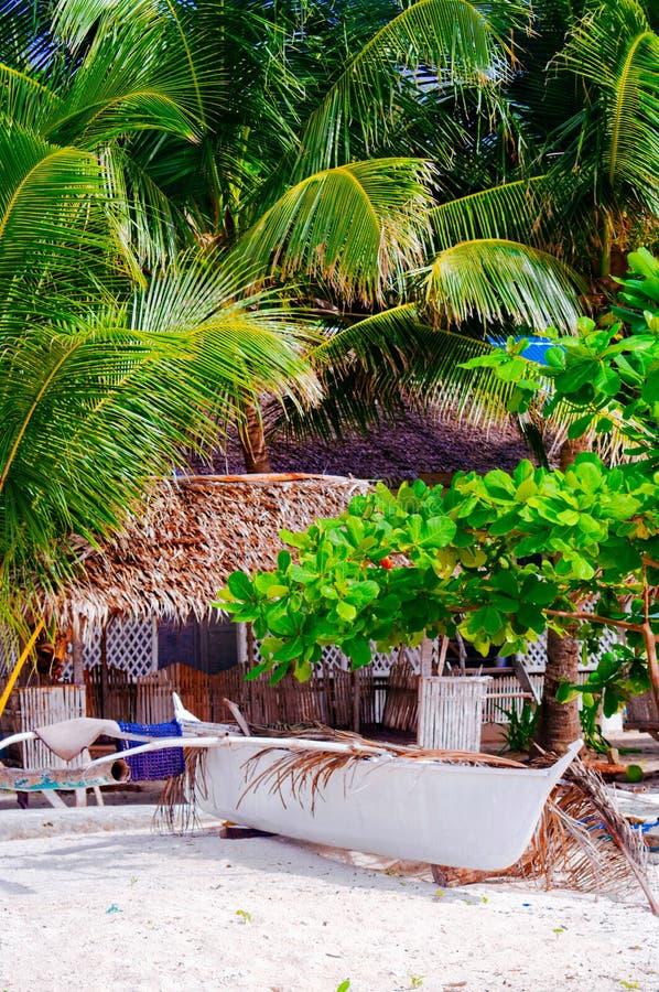 Fartyg på den tropiska vita sandstranden i Asien framme av det infödda huset, fiskebåt som parkeras i sanden royaltyfria foton