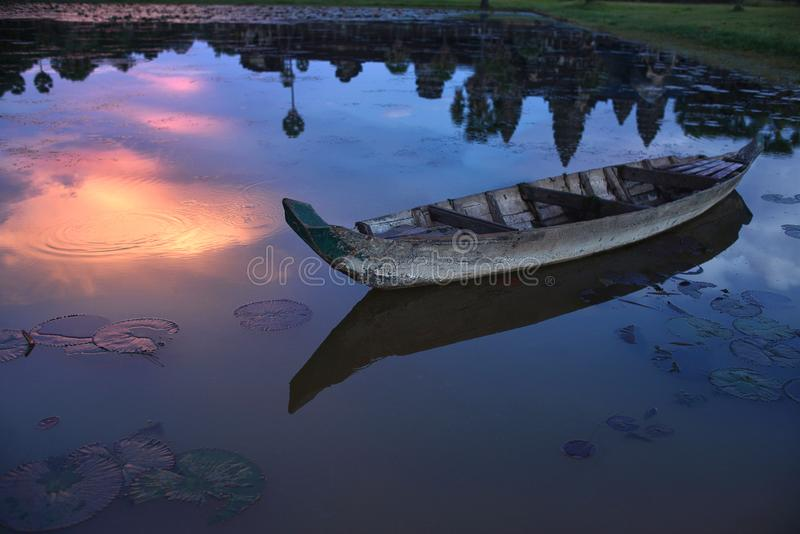 Fartyg på lotusblommadammet med reflexionen Angkor Wat i vatten på solnedgången, skymning, Siem Reap, Cambodja royaltyfria bilder