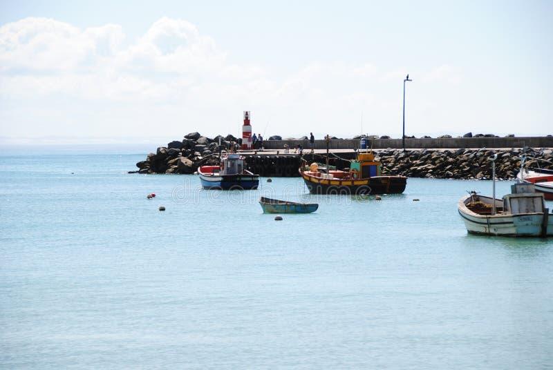 Fartyg på pir av udde Agulhas med fyren royaltyfri bild