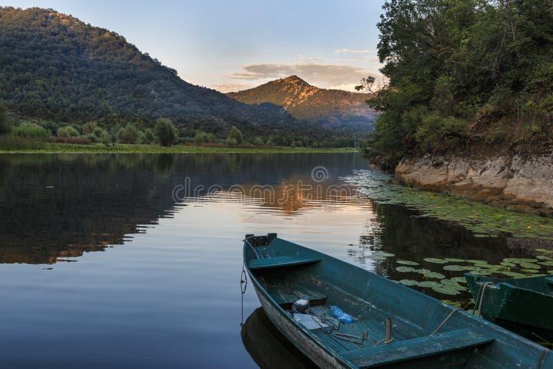 Fartyg på pir på solnedgången på en flod med berg arkivbild