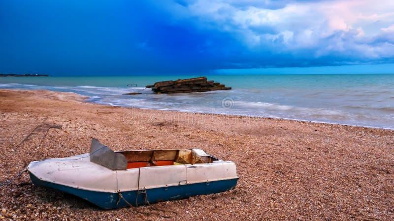 Fartyg på stranden för stormen clouds dramatiskt royaltyfri fotografi