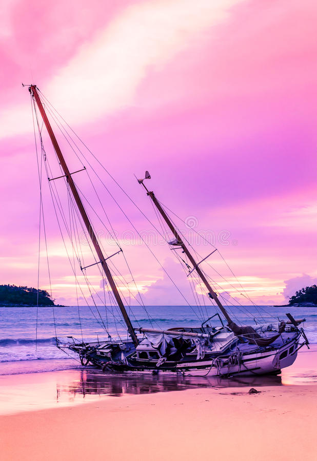 Fartyg på stranden i skymning och färgrikt av solnedgången fotografering för bildbyråer
