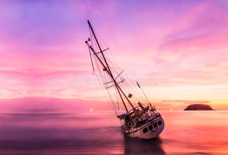 Fartyg på stranden i skymning och färgrikt av solnedgången arkivbild